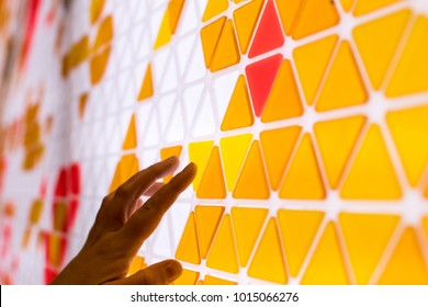 Tessellation einer Ebene mit gelben, orangefarbenen und roten Dreiecken auf weißem Hintergrund. mathematisches und künstlerisches Spiel, um eine Oberfläche mit geometrischen Formen zu bedecken. Kinder spielen Mathespiele mit der Hand