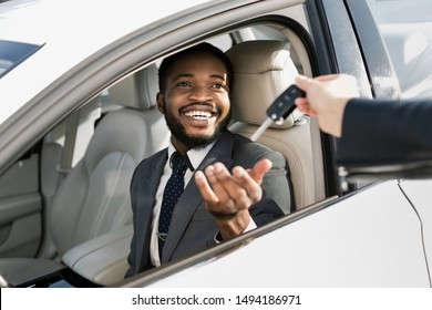Test drive new car. Young businessman taking auto key, sitting on driver's seat