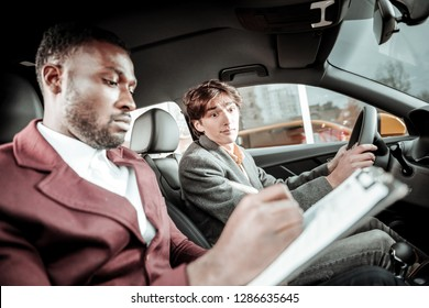 Test driving. Bearded professional driving instructor putting marks after test driving