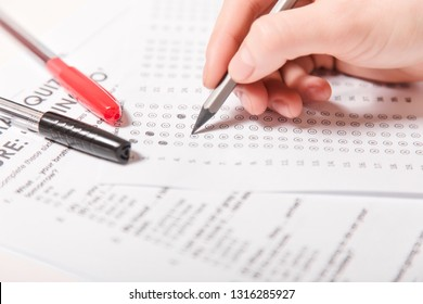 Test of English multiple choice on table.Woman takes an entrance exam