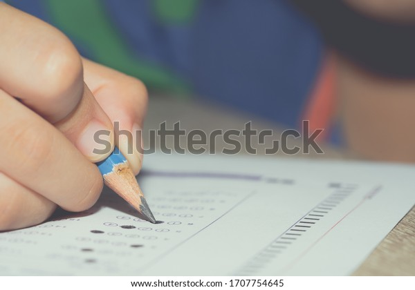 Test exam student kid, pencil writing answer on paper answer of question in examination test. It assessment intended to measure knowledge, skill, aptitude, physical fitness, or classification students