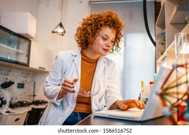 Test results. Serious smart female biologist sitting at the table and looking at the laptop screen while studying test results. Young Caucasian female scientist using laptop