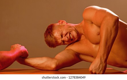A test of strength. Men competitors try to win victory or revenge. Strength skills. Twins men competing till victory. Twins competitors arm wrestling. Revenge in sport.