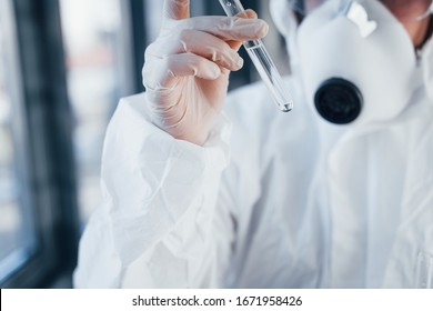 With test tube in hand. Female doctor scientist in lab coat, defensive eyewear and mask standing indoors.
