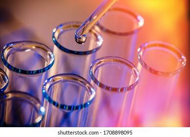Test tube row. Concept of medical or science laboratory, liquid drop droplet with dropper in blue red tone background, close up, macro photography picture.