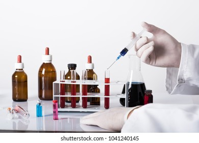 test tubes and laboratory tests with colored liquids, hand in glove holding test tube