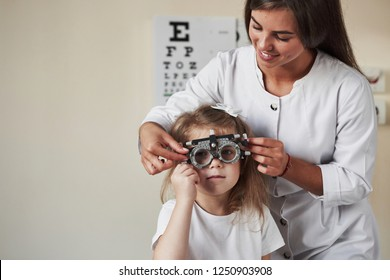 Testing what's better for his eyes. Doctor checking little girl sight and tuning the phoropter.
