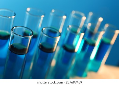 Test-tubes filled with blue and red fluid on the muted background