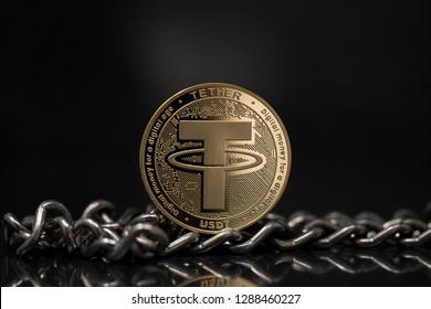 Tether USDT cryptocurrency physical coin placed next to metal chain on reflective surface in the black background