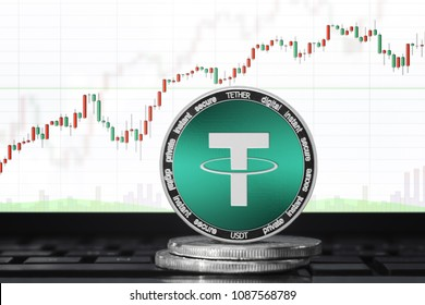 TETHER (USDT) cryptocurrency; physical concept tether coin on the background of the chart