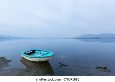 tethered anchored boat with a calm blue tranquil lagoon background setting