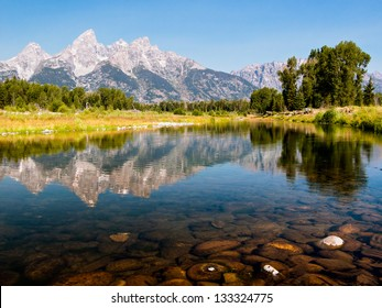 The Teton Mountain Range is reflected in the shallow and still waters of a braid of the Snake River in Grand Teton National park, Wyoming, USA