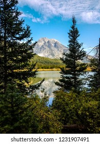 The Teton mountains in the distance and the forested shoreline create a stunning reflection in Leigh Lake at Grand Teton  National Park in Wyoming.