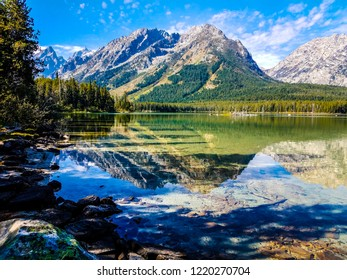 Teton mountains are in full view across Leigh Lake in Grand Teton NP in Wyoming. Reflections of clouds, mountains, and sky are perfectly etched into the lake waters. Shadows provide great contrast.