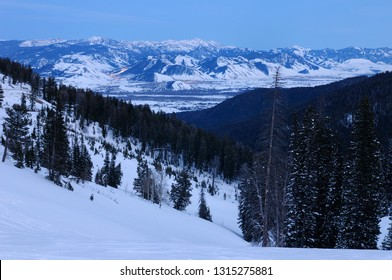 Teton Pass at dusk with lights of Jackson and the Rocky Mountains Jackson and Pinnacle Peaks in winter