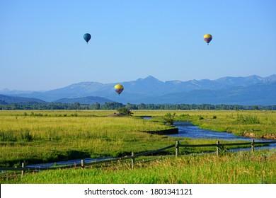 TETON VILLAGE, WY –2 AUG 2020- View of three hot air balloons near Teton Village, a mountain resort located near Grand Teton National Park in Jackson, Wyoming, United States.