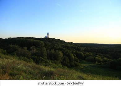 Teufelsberg NSA listening towers at sunset.  Towers on hill, blue sky and green forest.