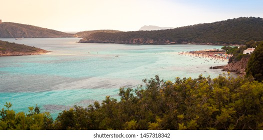 Teulada, Sardinia. Tuerredda beach at sunset with swimmers in the sea. Beach with white sand in Caribbean style.