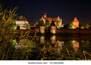 Teutonic Castle of Malbork under starry sky at night