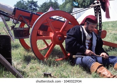 Tewksbury Gloucestershire UK 1994. An unidentified re-enactor of the Tudor Wars wears the period clothing of a Tudor Gunner he sits against a cannon while sharpening a blade at a re-enactment event.