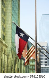 Texas and American flags on building flagpoles, flying in the middle of the central business district of downtown Dallas, TX.
