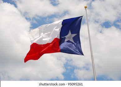 Texas flag in bright sunshine on very windy day with blue sky and puffy clouds.