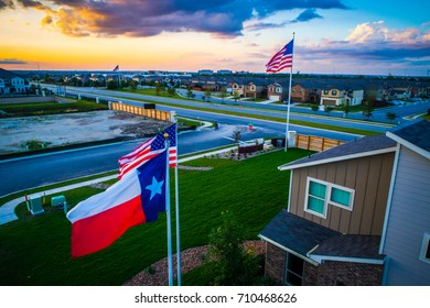 Texas Flag in the Foreground with American Flag high in the background with New home about to hit the market in Austin Texas USA aerial drone view of new suburb development perfect Living in America