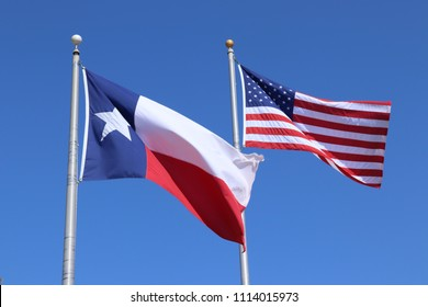 Texas flag, Lone Star State flag and United States of America US flag against blue sky background