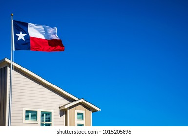Texas flag on perfect flagpole flying in front of brand new modern home in new suburb in Austin , Texas the capital city of Texas in the Lone Star State