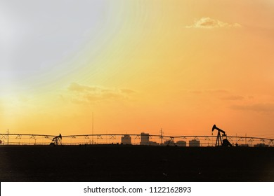 Texas heat. Silhouettes of pump jacks, city skyline, and irrigation system with orange sky.