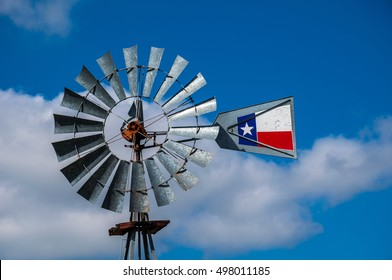 Texas Historic Windmill made from Metal or Tin with a Texas Flag painted on Tail with Blue sky background and a few puffy clouds in the Lone Star State