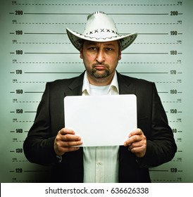 Texas man with white hat and cigar posing for police mugshot