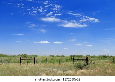 Texas prairie with barbed wire fence and blue skies