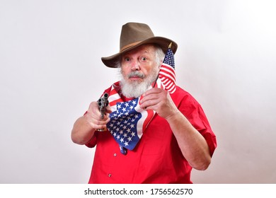 Texas rancher wearing a patriotic bandana, waving an American flag and ready to defend his propery.Old man with a floppy western hat and a six shooter waving the American flag for the 4th of July