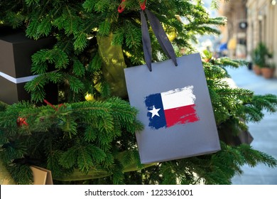 Texas state flag printed on a Christmas gift box. Printed present box decorations on a Xmas tree branch on a street. Christmas shopping in United States, local market sale and deals concept.