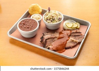 Texas style beef brisket served with barbecue sauce. Smoked brisket with beans, cornbread, and pickles.