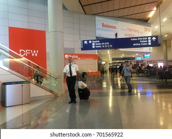 TEXAS, USA - AUGUST 19, 2017: An airplane captain wearing a uniform and carrying a suitcase walks in the terminal of Dallas Fort Worth International Airport, DFW, which is crowded with passengers.