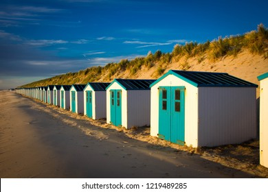 Texel. Little white-blue houses (cabins) in the dunes in Texel Holland Europe (Dutch Island Texel) during sunset.