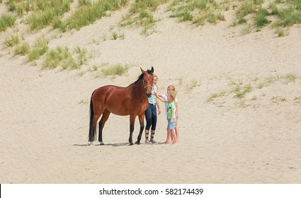 Texel, Netherlands, 1 August 2015: Horse with rider and two girls on the North Sea Texel beach