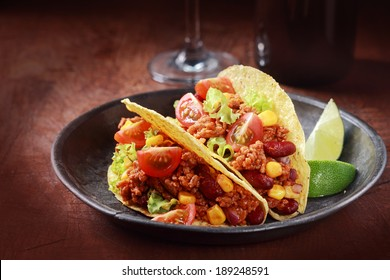 Tex-mex cuisine with a serving of two corn tacos with ground meat, salad and vegetable filling in a rustic wooden bowl with a garnish of lemon wedges