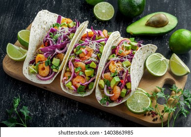 Tex-Mex fast food made of shrimps, avocado and onion. Tasty tacos on a wooden board.