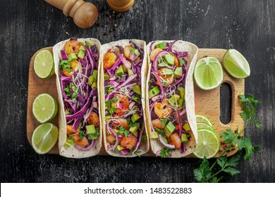 Tex-Mex fast food made of shrimps, avocado and onion. Tasty tacos on a wooden board. Top view shot, directly above.
