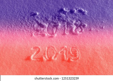 "Text ""2018"" and ""2019"" written on fresh snow colored in Ultra Violet and Living Coral pantone colors. New year holiday concept"