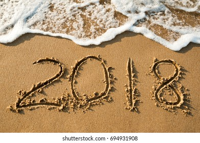 Text 2018 on a beach sand with wave. Concept New Year 2018 is begining