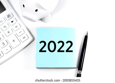 Text 2022 on sticker. Calculator, piggy and pen. Business and tax concept on white background. Top view.