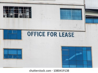 Text about renting free office space in the building. Advertise for renting offices on facade of the house in Saigon.