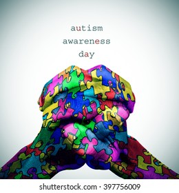 text autism awareness day and the hands of a man put together patterned with many puzzle pieces of different colors, with a slight vignette added