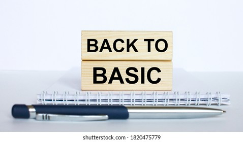 The text BackTo Basic on a bar of wood, lying on a Notepad with a metal blue pen. Business concept photo