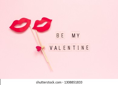 Text Be my Valentine and couple paper lips props on stick fastened clothespin heart on pink background. Concept lesbian love Creative Valentine's Day, Valentine card Top view Flat lay
