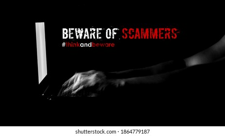 """A text """"Beware of scammers. #think and beware"""" with low key motion blur male hand typing on keyboard laptop in the dark background. Concept for scammers awareness and cyber security."""